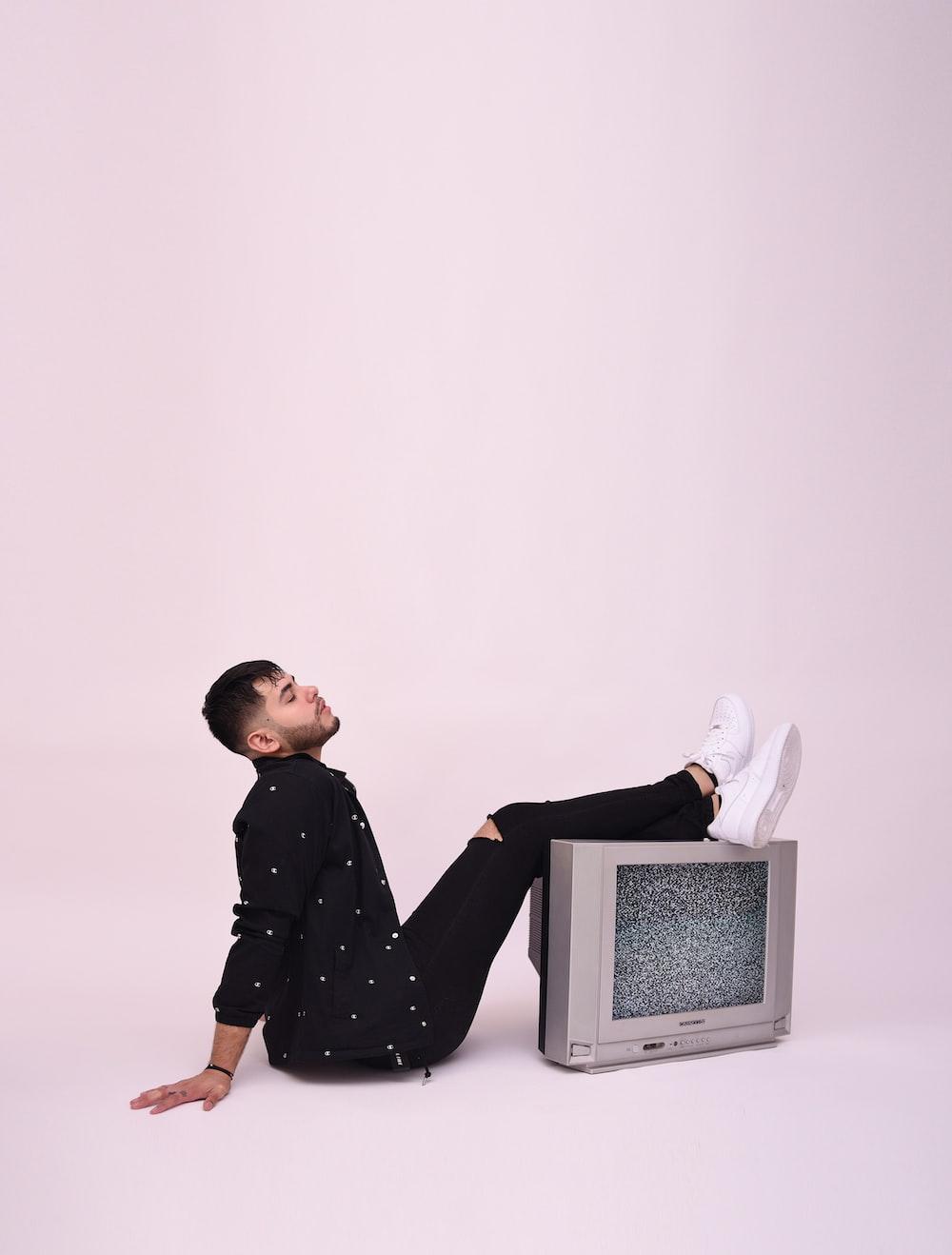 boy in black and white polka dot long sleeve shirt sitting on white chair