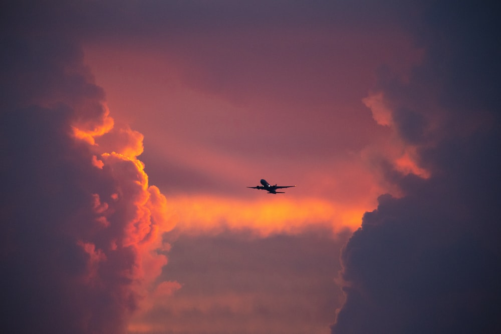 airplane flying in the sky during sunset