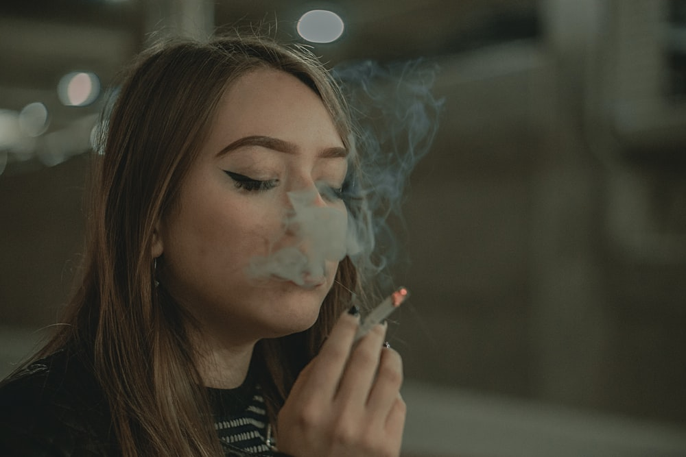 woman in black and white striped shirt smoking cigarette
