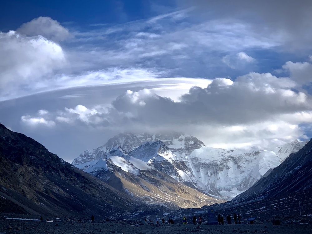 white clouds over snow covered mountains