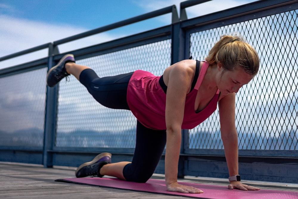 woman in red tank top and black leggings doing yoga