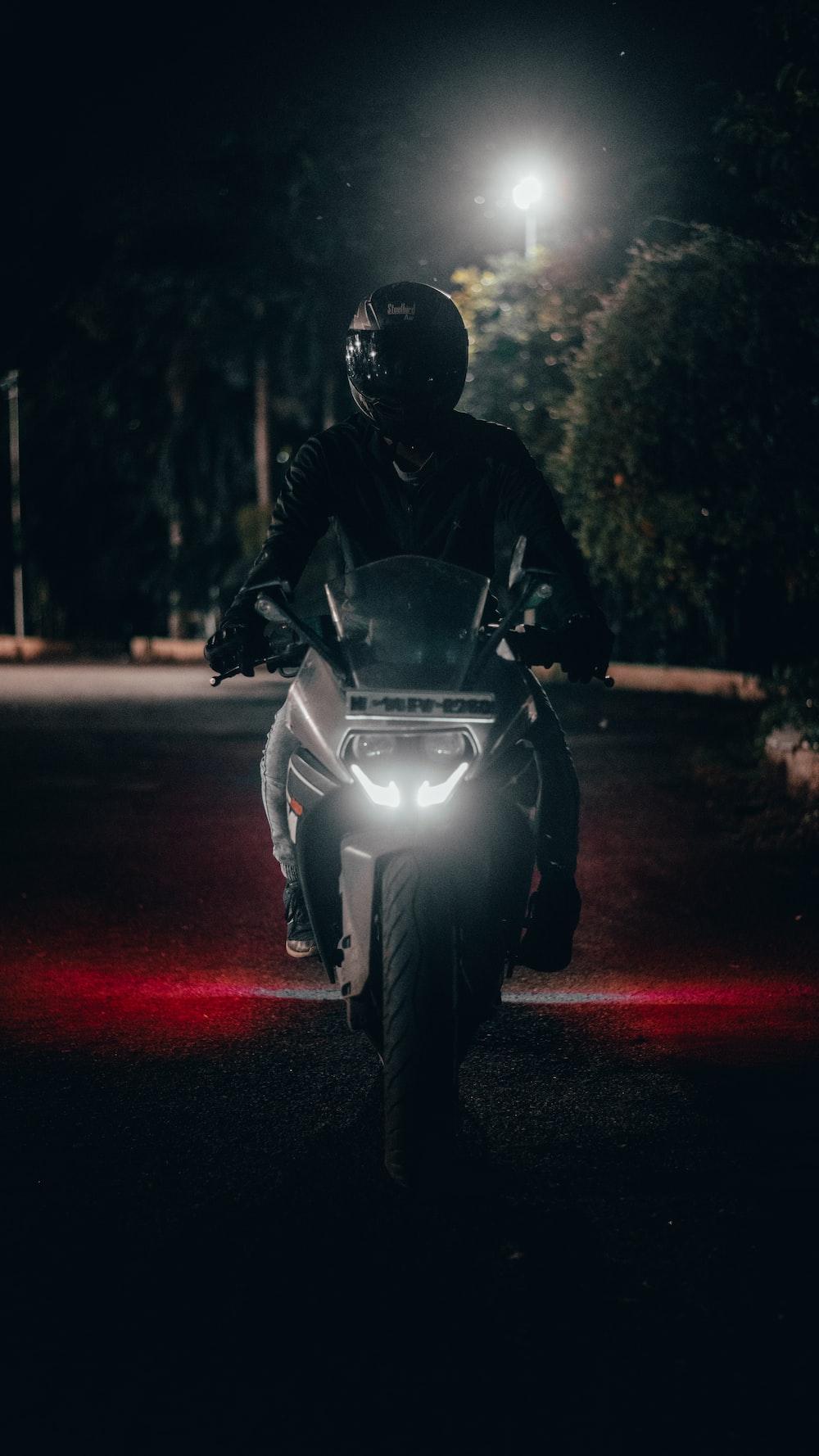 man in black jacket riding on motorcycle during night time