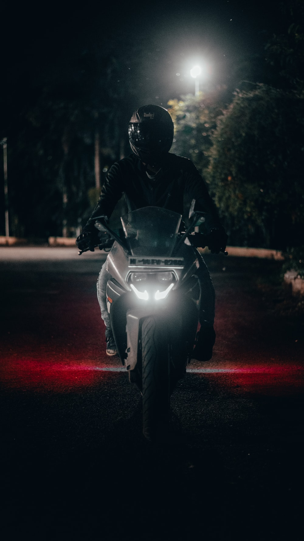 man in black jacket riding on motorcycle during night time