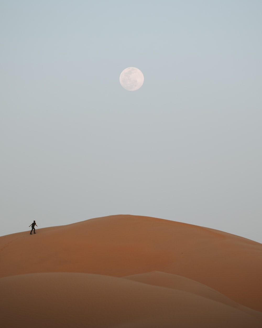 man standing on desert under full moon
