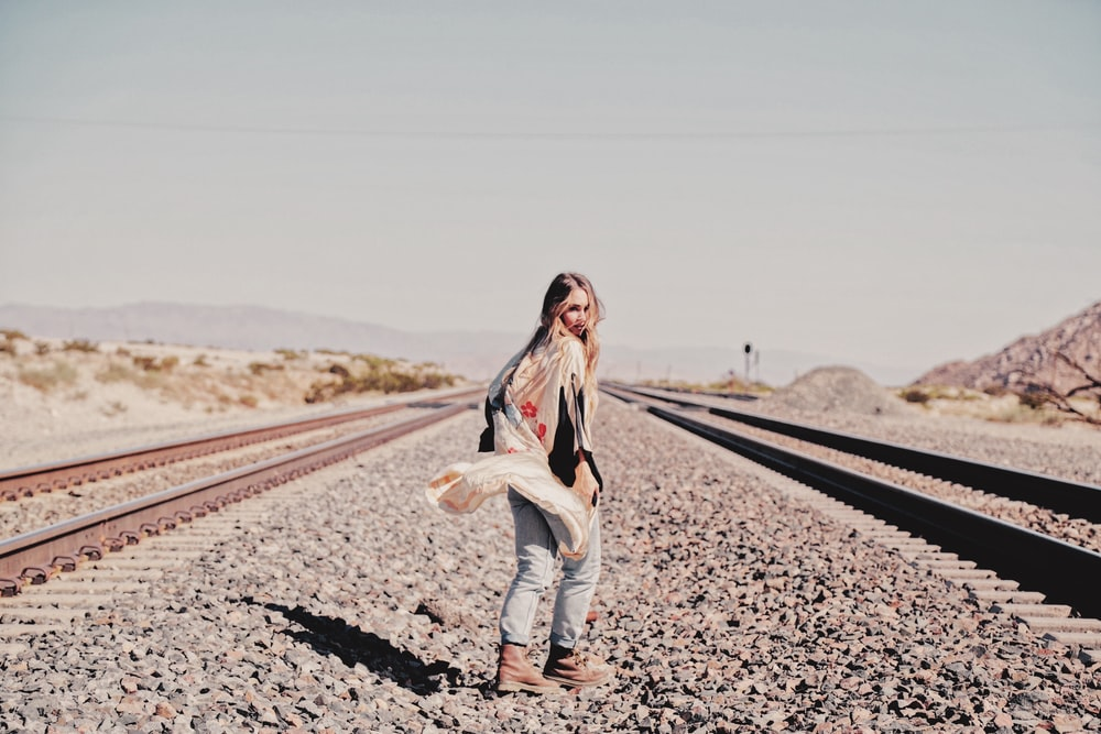 woman in white long sleeve shirt and blue denim jeans standing on road during daytime