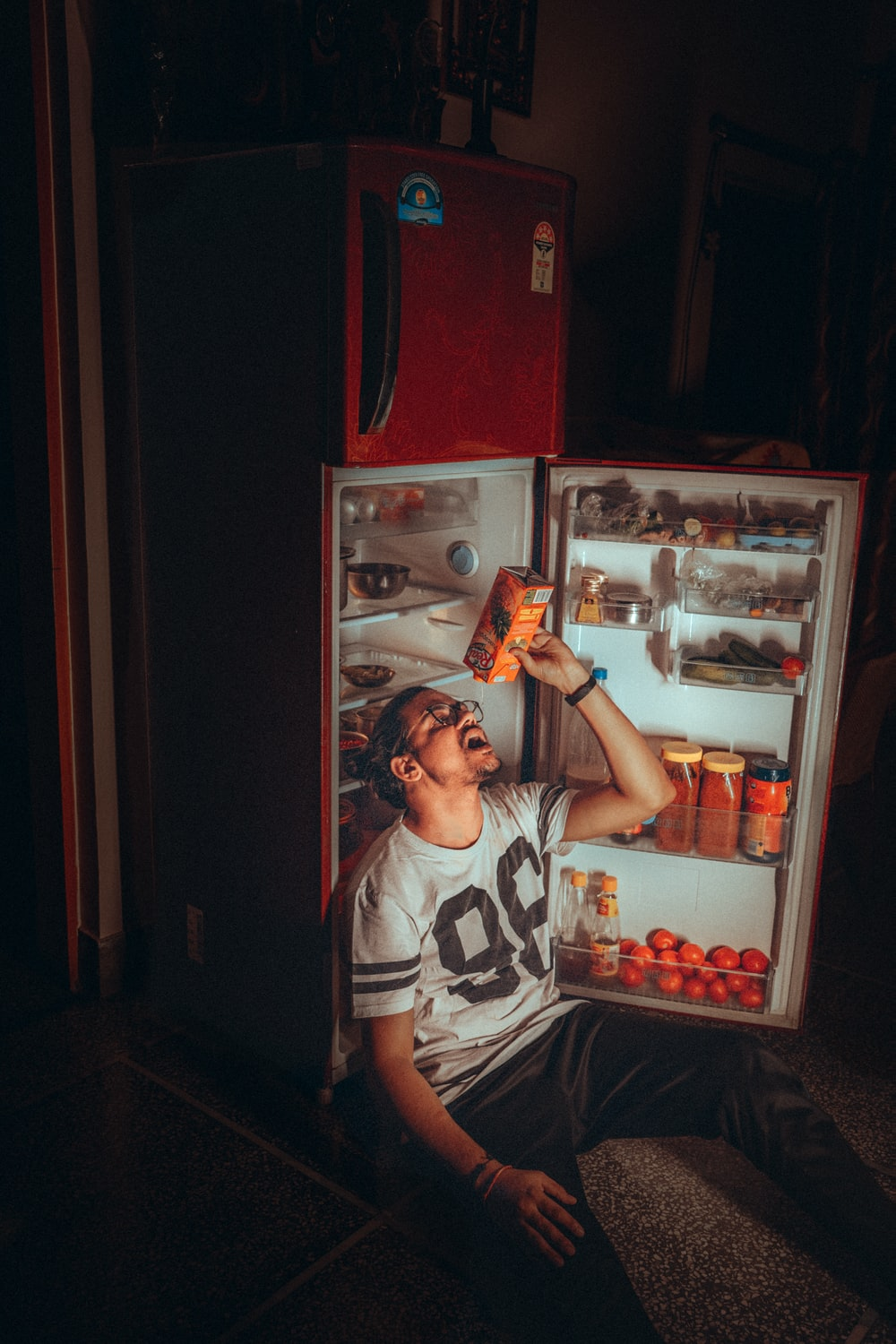 boy in white and black tank top standing beside red top mount refrigerator
