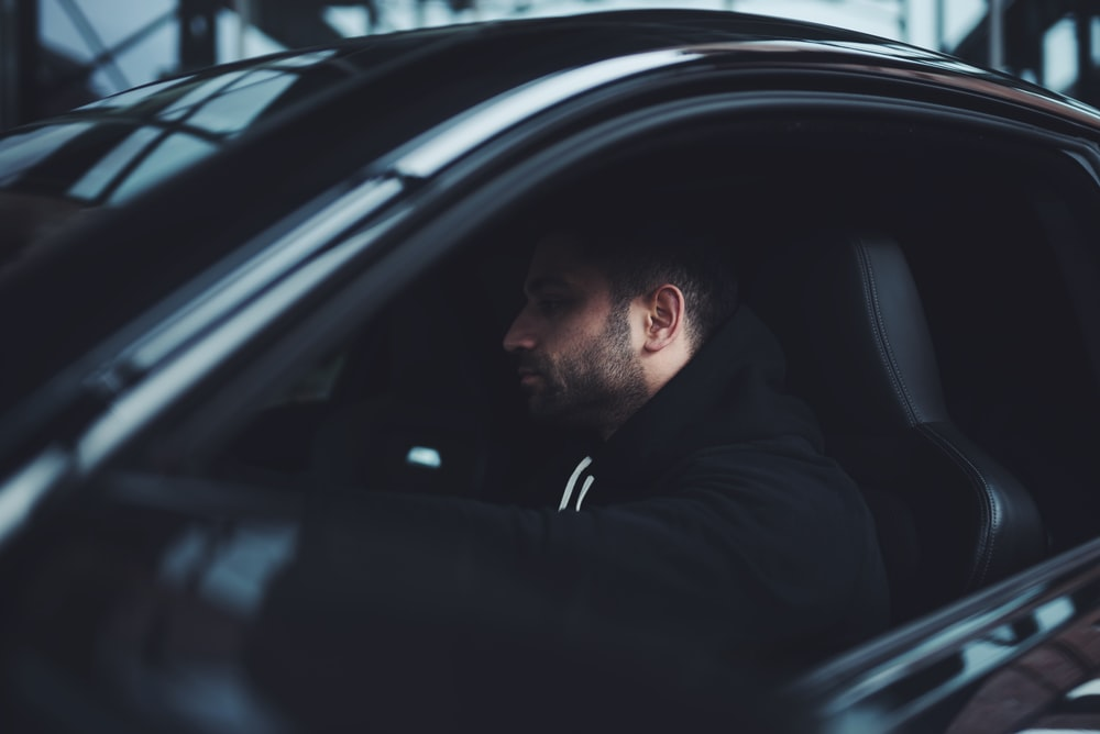 man in black hoodie inside car