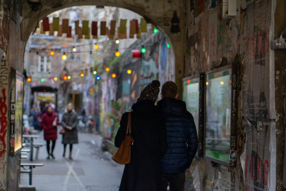 woman in black jacket walking on sidewalk during daytime