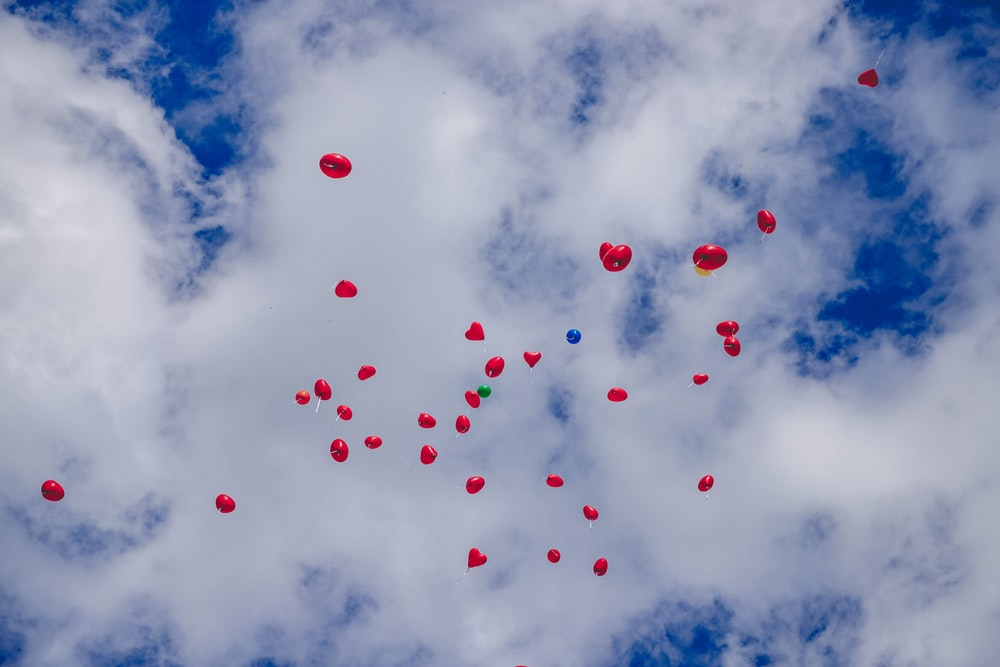 red balloons on blue sky during daytime