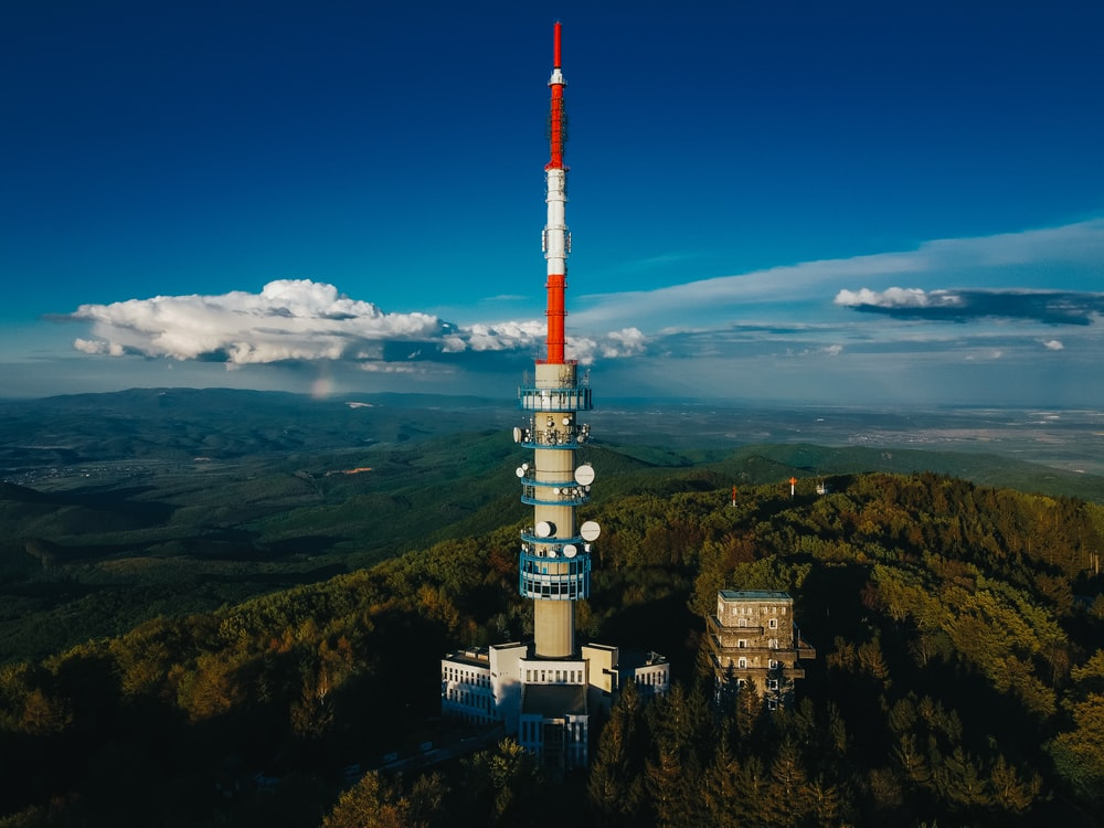 white and red tower on top of mountain under blue sky during daytime