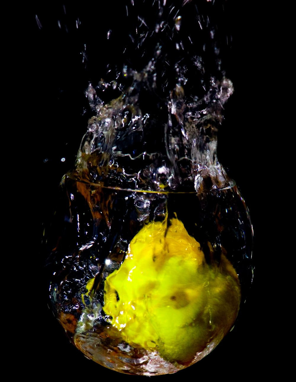 yellow fruit in water with water droplets