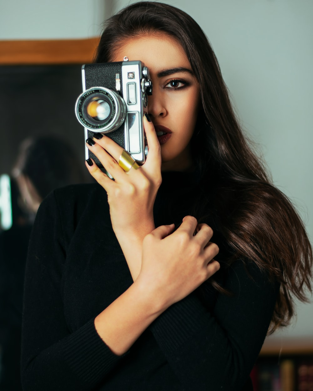 woman in black long sleeve shirt holding gray and black camera