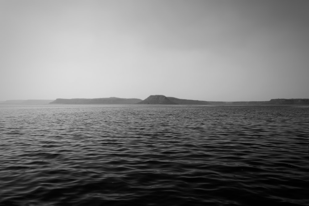 grayscale photo of mountain near body of water