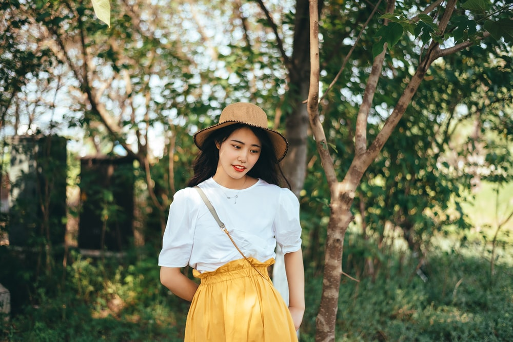 girl in white shirt and yellow skirt standing under green tree during daytime