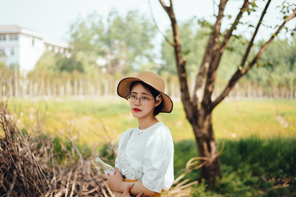 woman in white dress shirt and brown hat standing near green grass during daytime