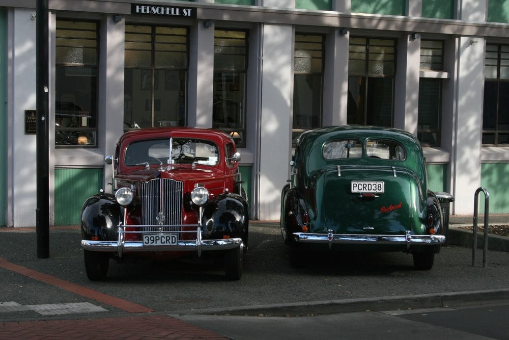 vintage green and red car parked on the street