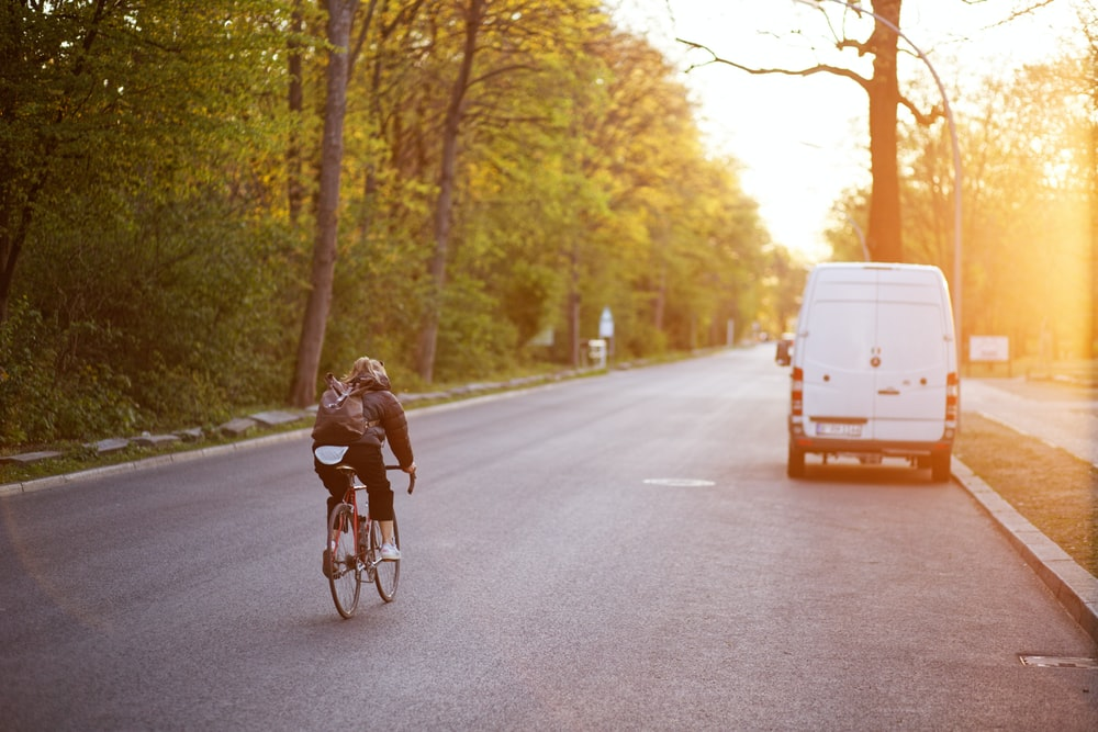 woman in black jacket riding bicycle on road during daytime