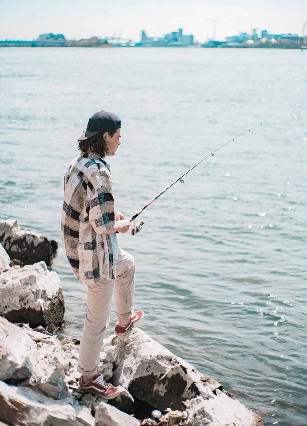 man in blue and white plaid dress shirt and brown pants fishing on sea during daytime
