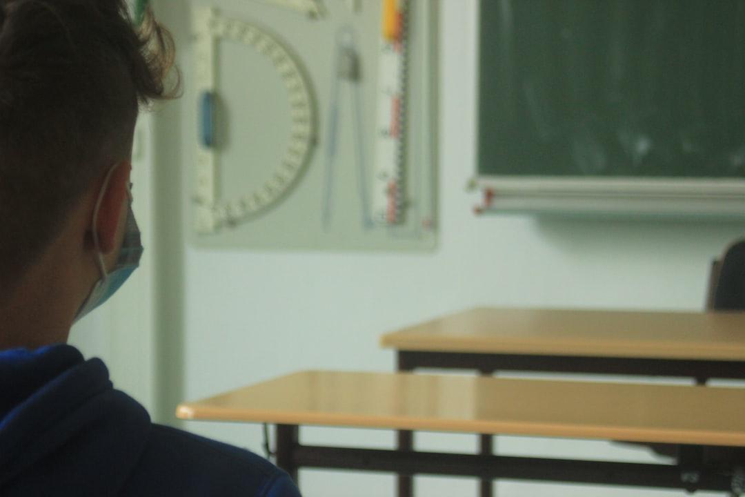 Junge sitzt mit einem Mundschutz in der Schule.