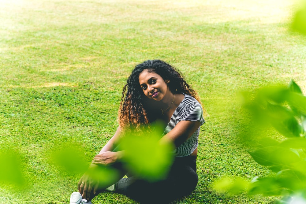 woman in black and white stripe shirt lying on green grass field during daytime