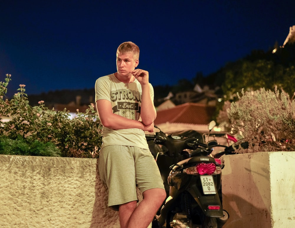 man in brown tank top and brown shorts standing beside motorcycle during daytime