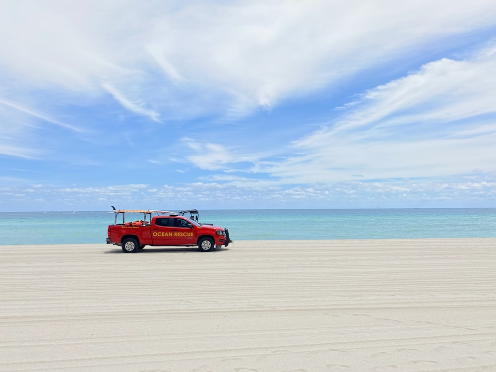 red suv on beach during daytime