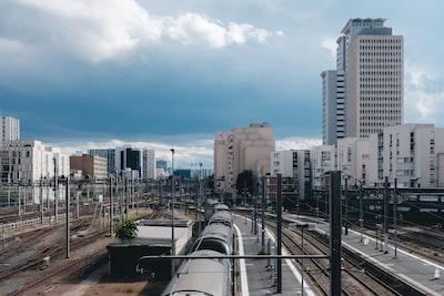 gray metal train rail near city buildings during daytime