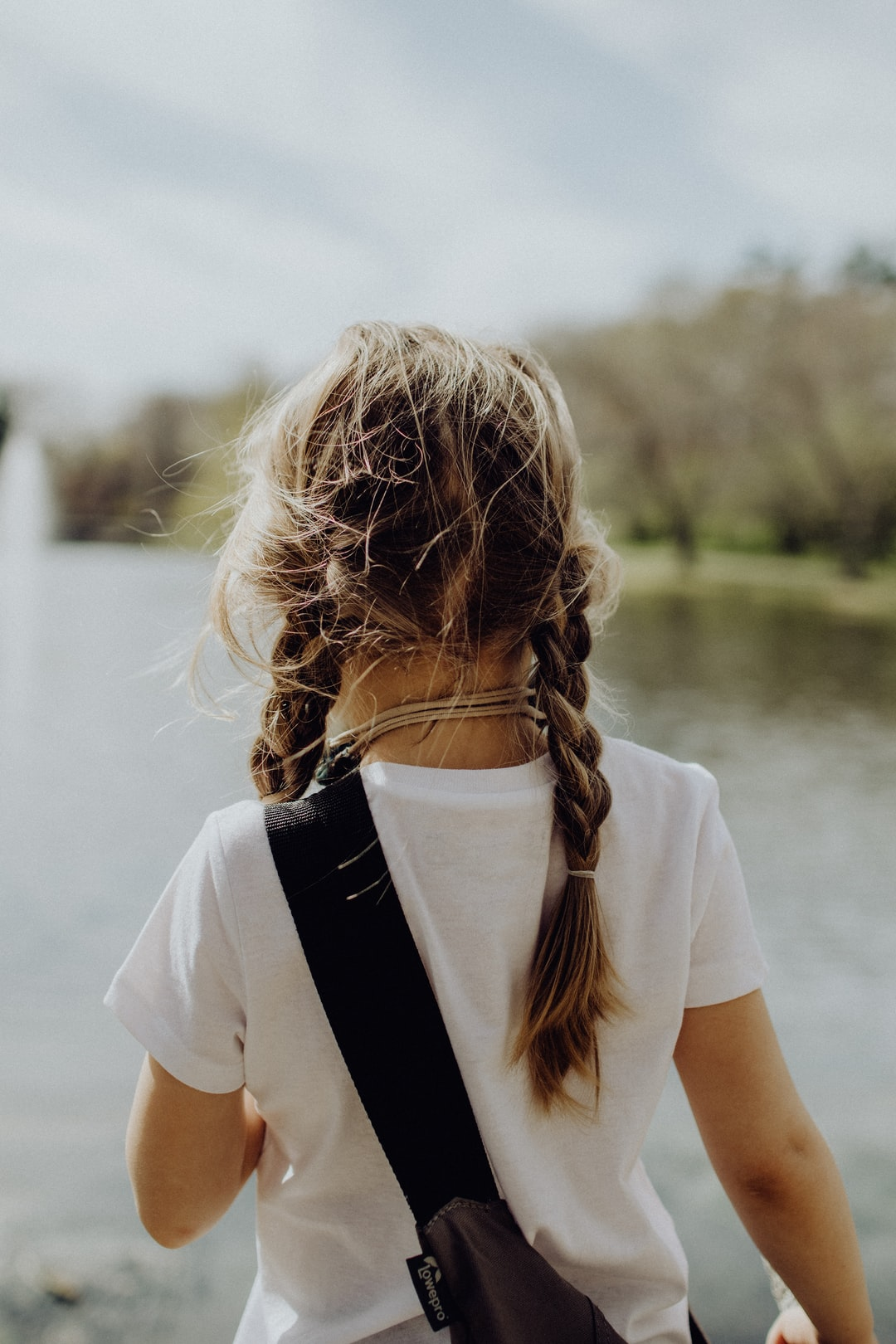 Little girl in a white T shirt with braids and a bag slung over her shoulder