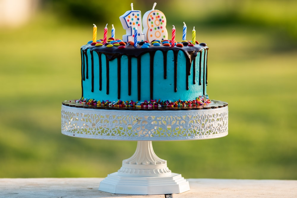 blue and white cake with happy birthday candles