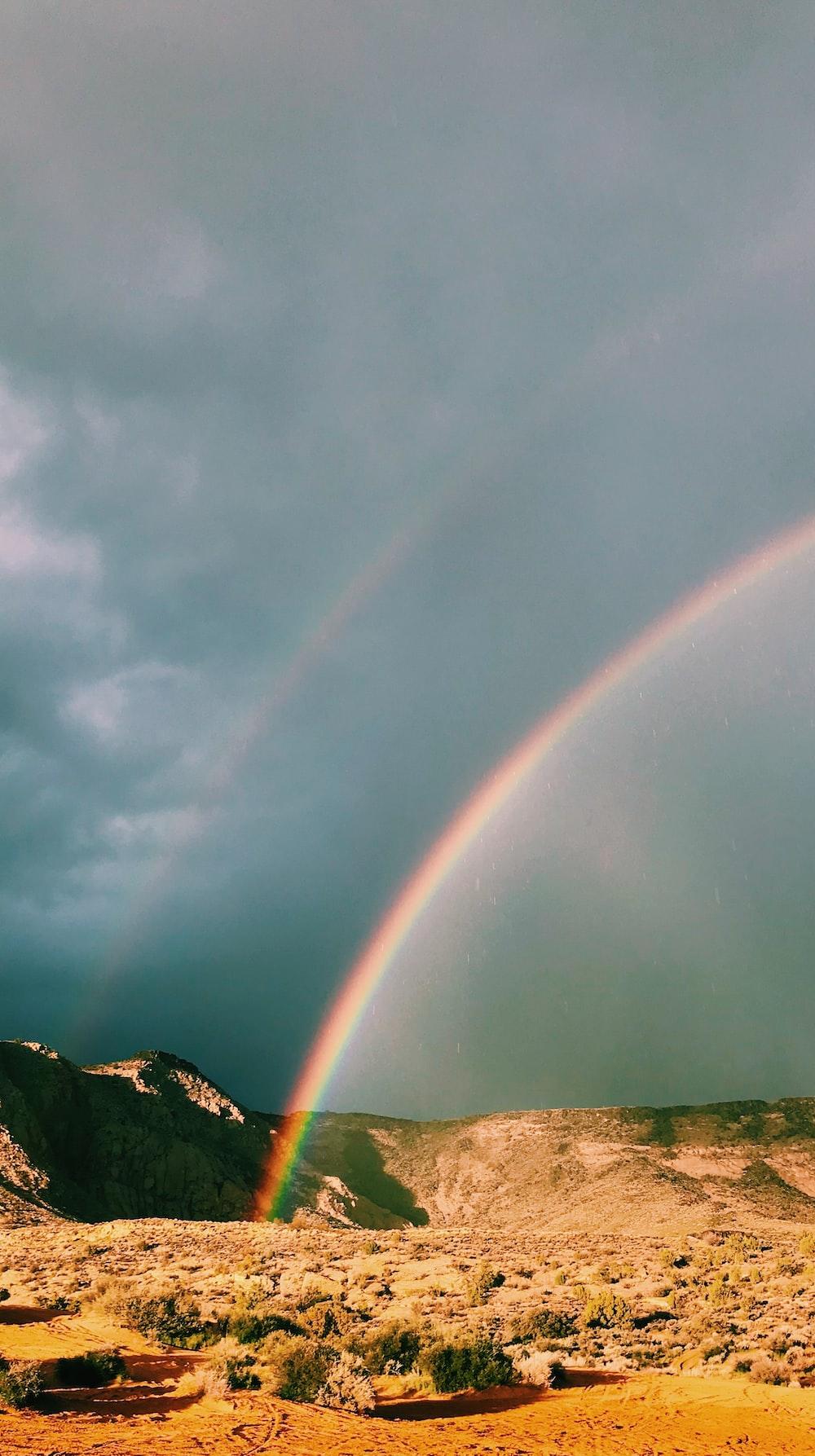 green mountain under rainbow during daytime