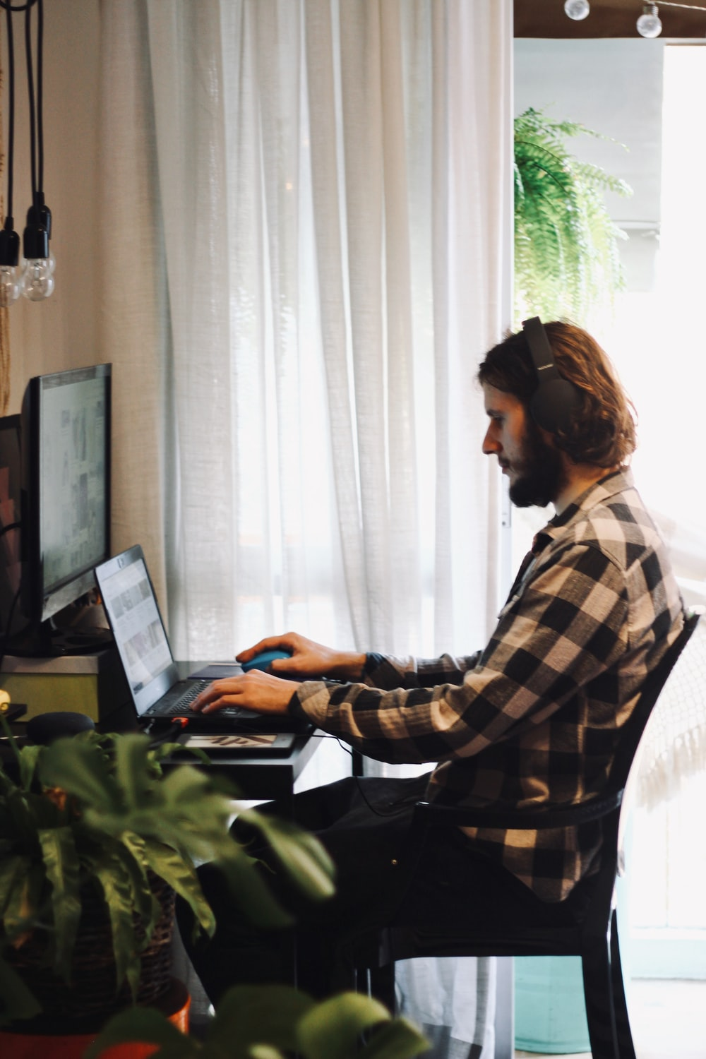 woman in black and white plaid dress shirt using laptop computer