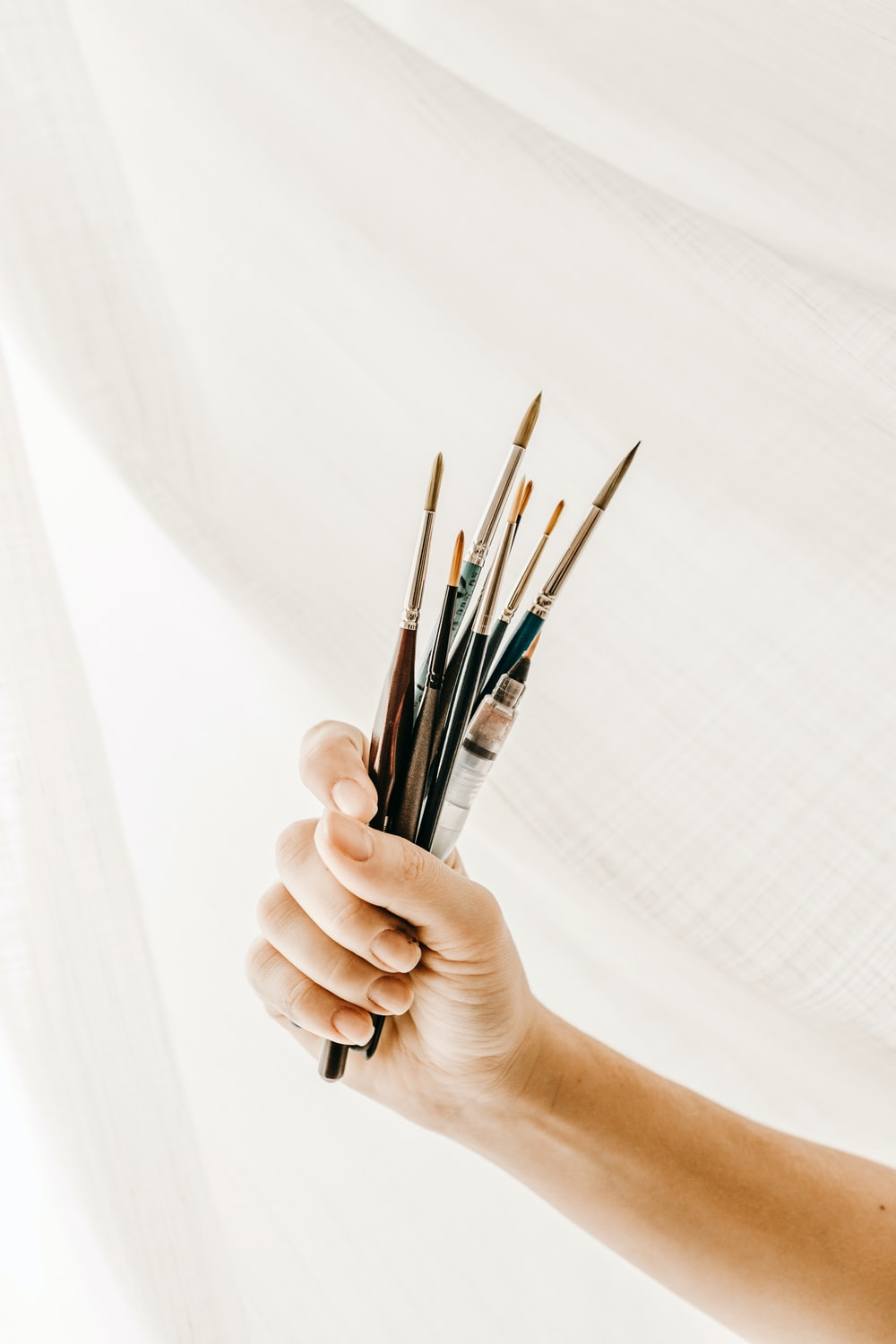 person holding paint brush and brush