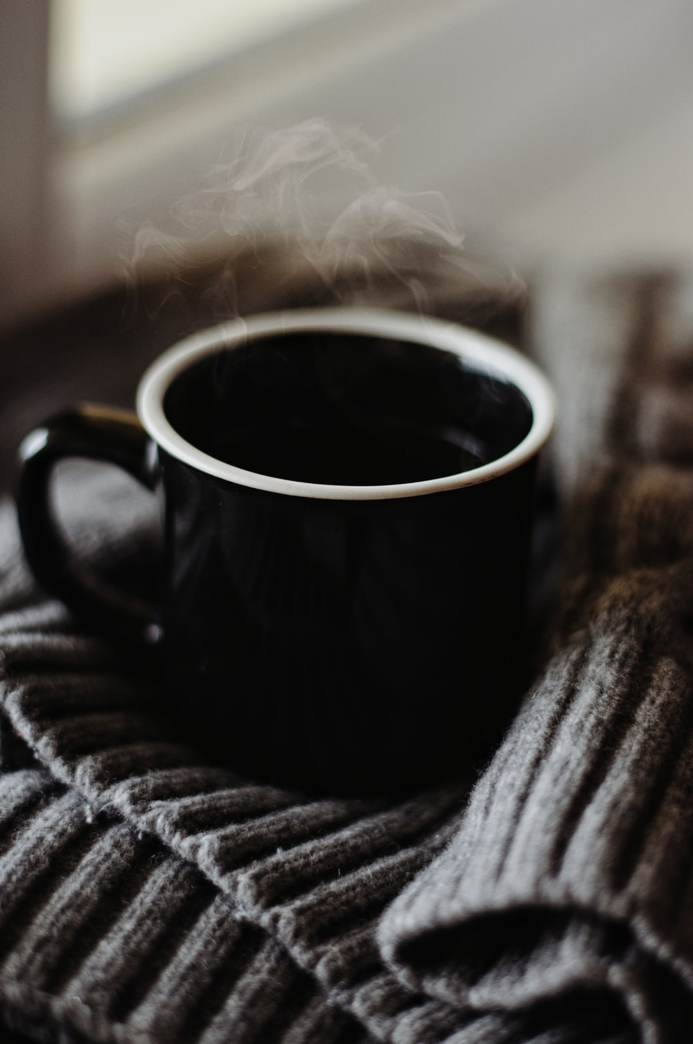 black and white ceramic mug on brown and black textile