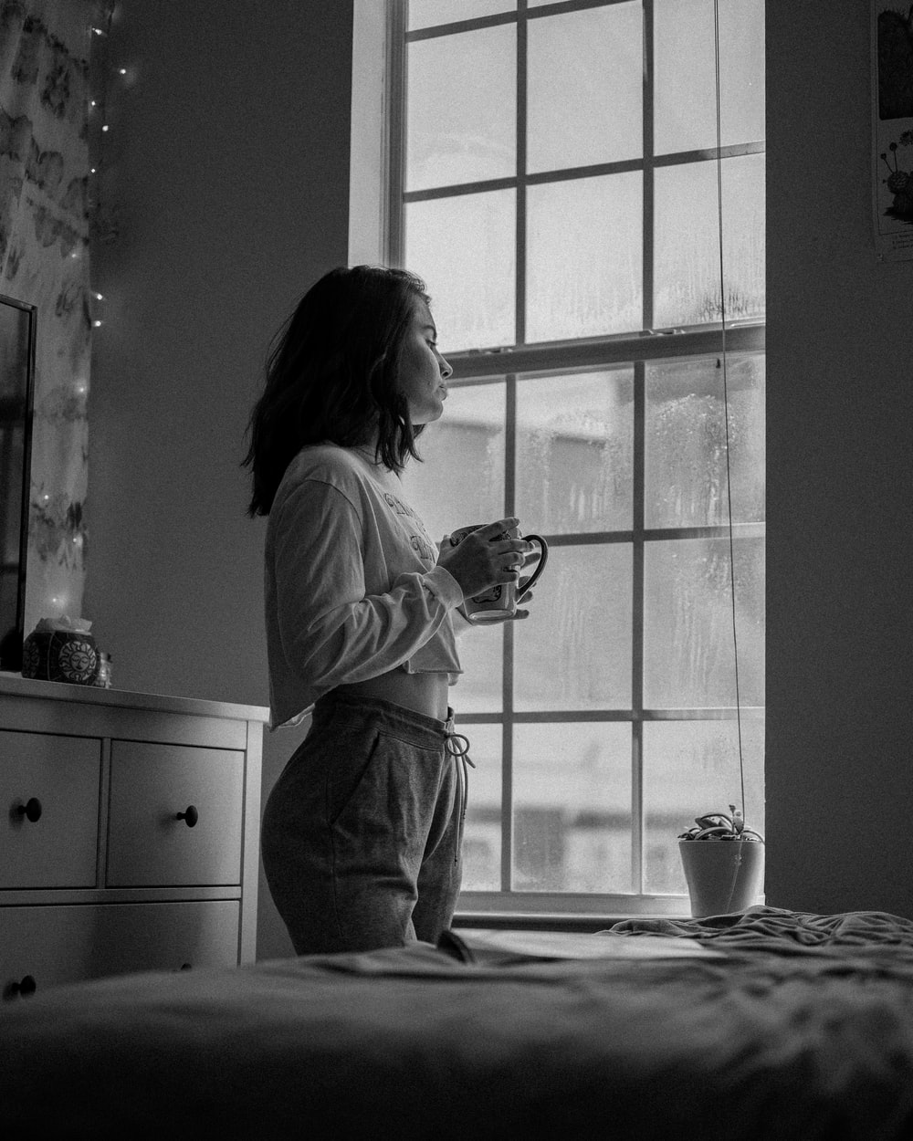 woman in white long sleeve shirt holding mug in grayscale photography