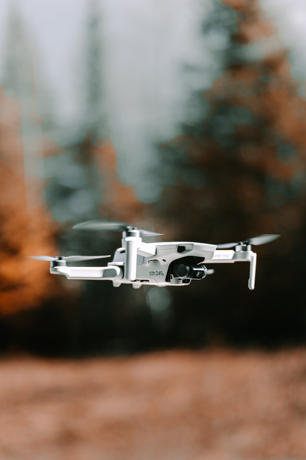 gray drone flying in mid air during daytime