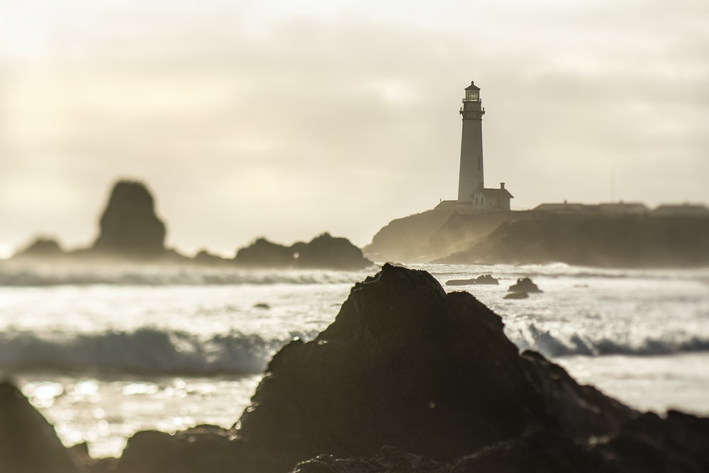 white and black lighthouse on black rock formation near sea during daytime