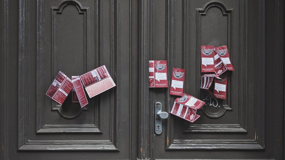 red and white plastic packs on brown wooden door