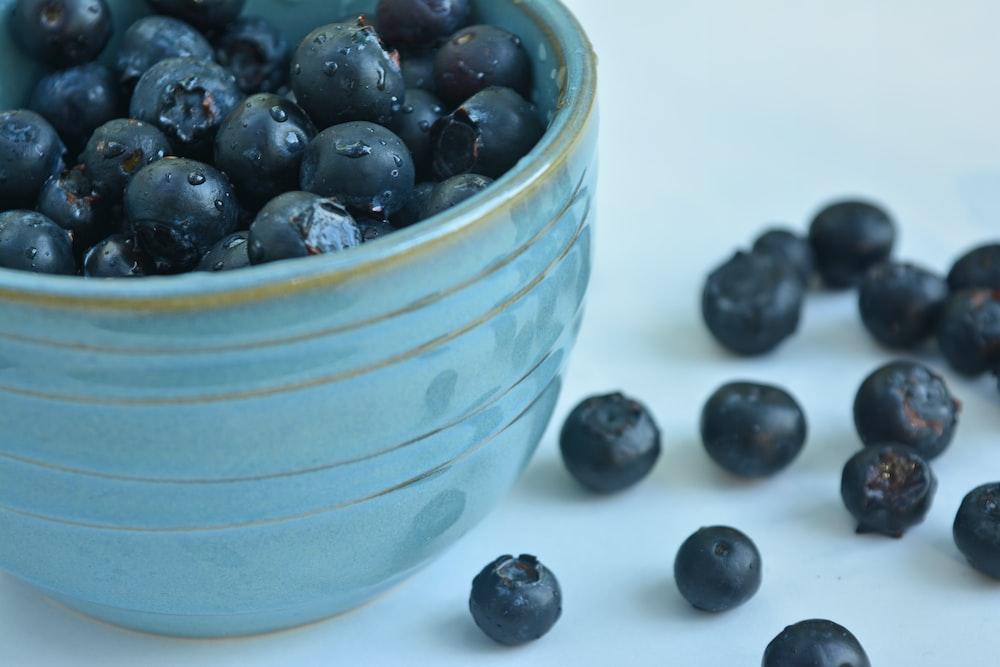 black berries in blue ceramic bowl