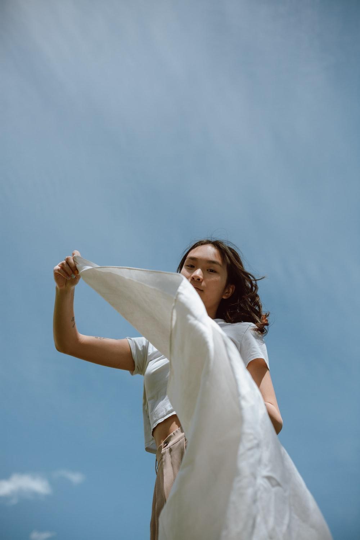 woman in white dress holding white textile