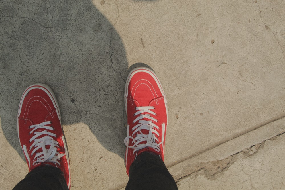 person in red and white nike sneakers