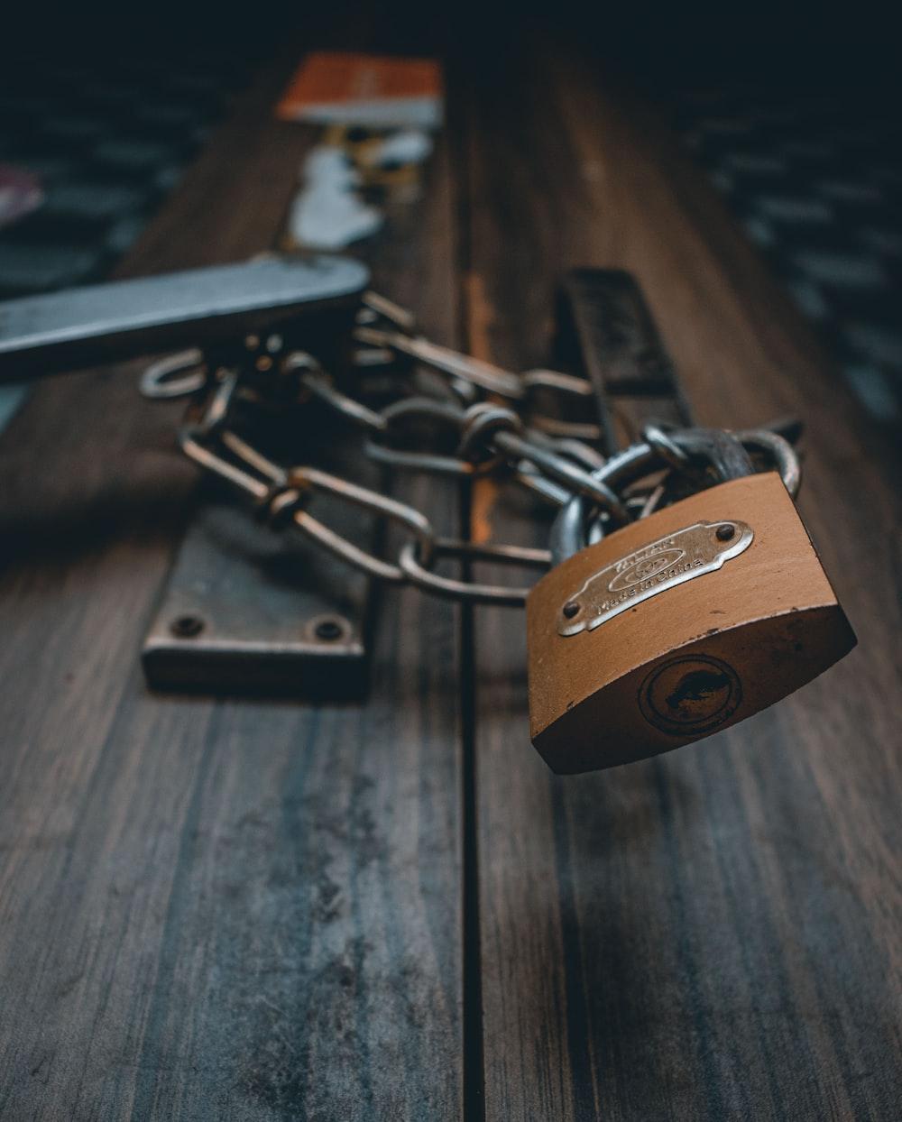 brown padlock on brown wooden surface
