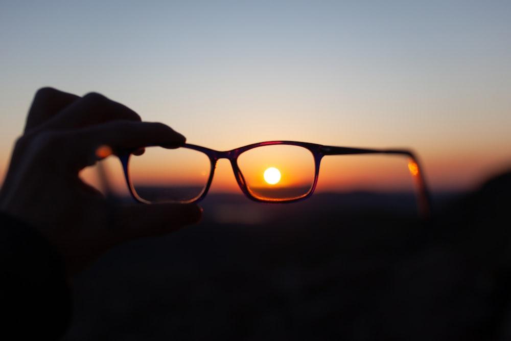 person holding brown framed eyeglasses