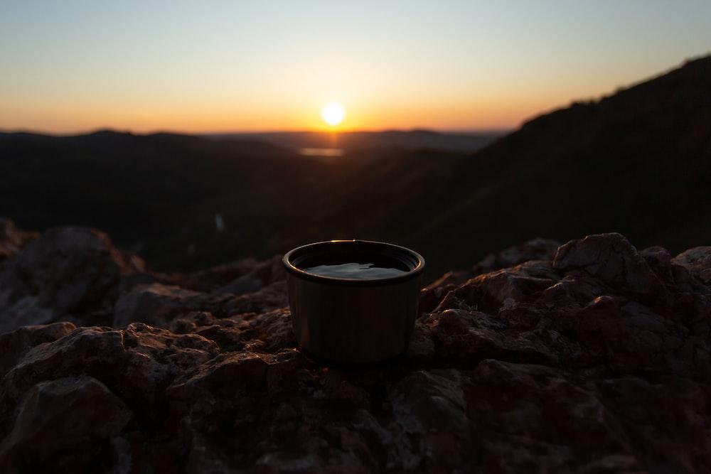 black ceramic mug on rocky mountain during sunset