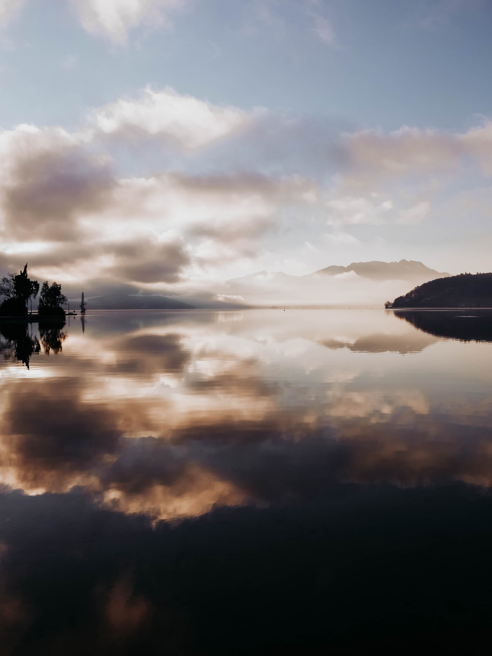 silhouette of boat on calm water under cloudy sky during daytime