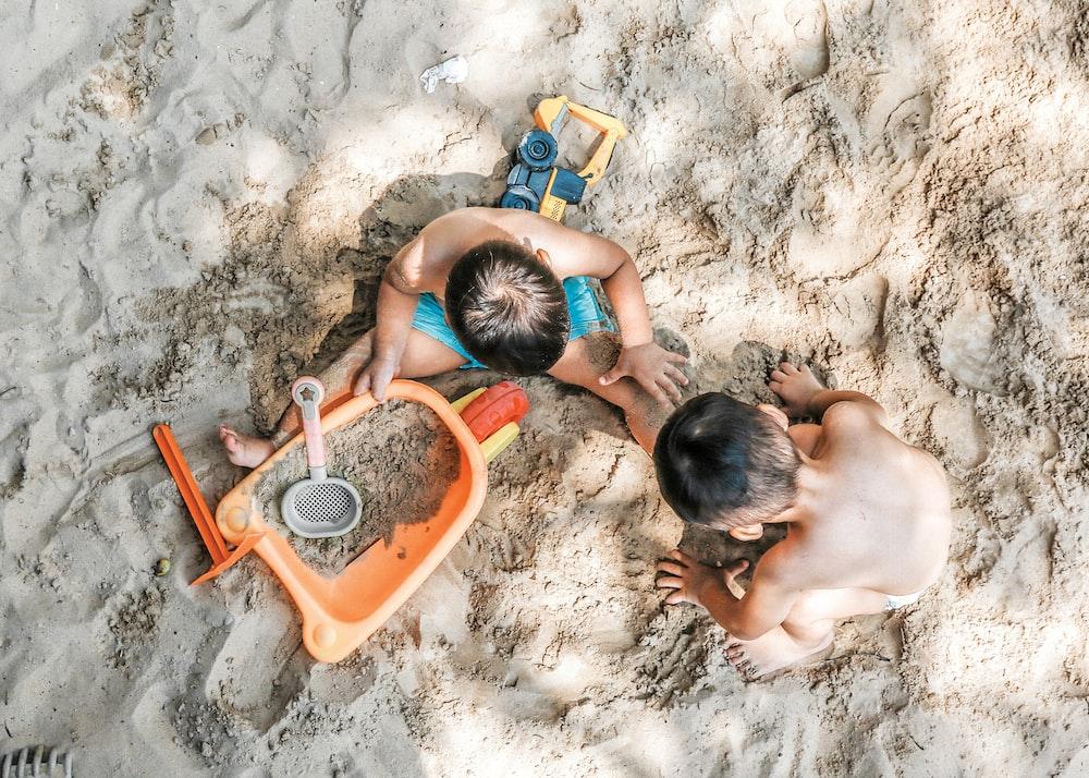 2 boys sitting on sand