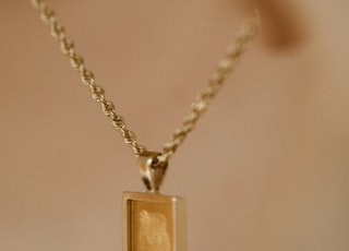 gold rectangular pendant necklace on white surface