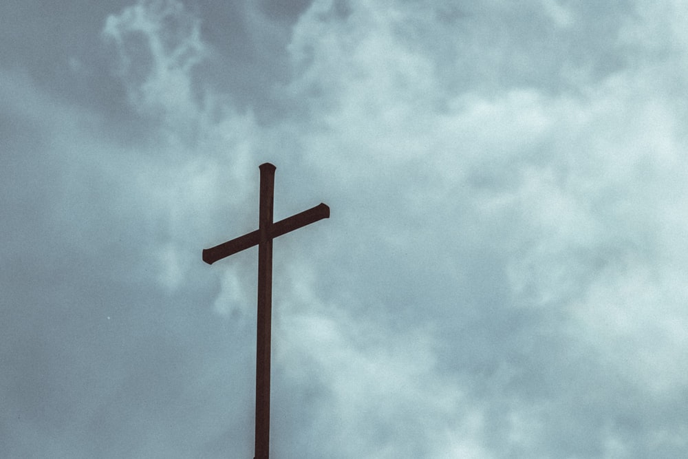 brown wooden cross under cloudy sky during daytime