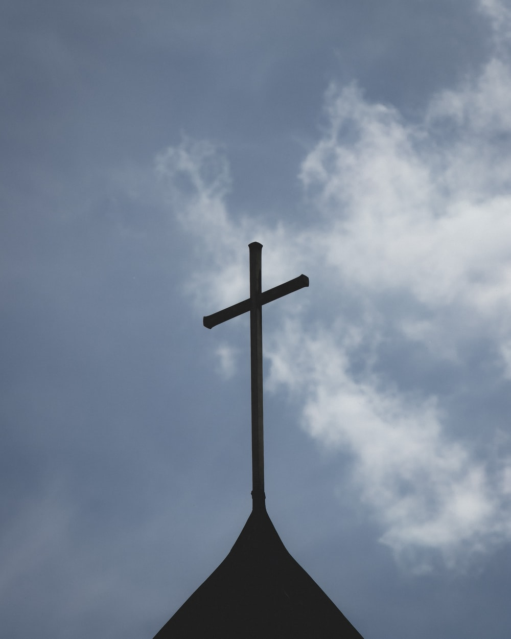 brown wooden cross under white clouds and blue sky during daytime