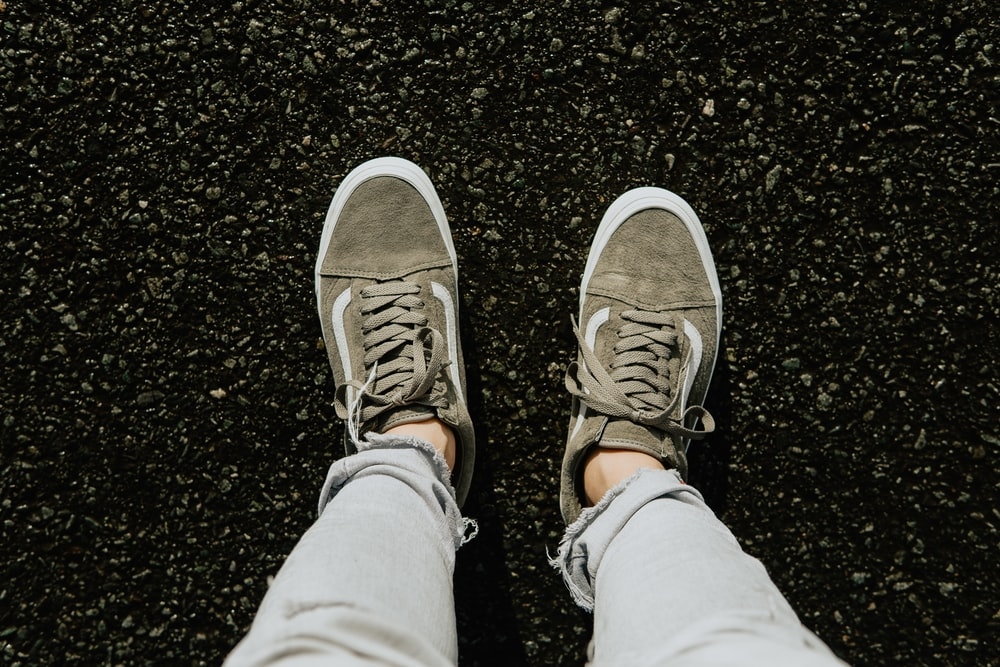 person in gray pants wearing brown and white sneakers