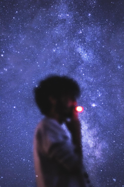 man in gray hoodie standing under starry night